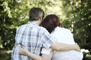 two white people are seen hugging/leaning on each other from behind while sitting next to each other; the male on the left has a plaid shirt and brown hair; the female on the right has a white shirt and reddish hair; trees and foliage are in front of them
