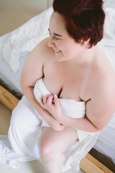 color pic of kirsten sitting on the edge of the white bed wrapped in a white sheet a la a mermaid; short red hair; pic is taken from above; K is looking away white smiling and laughing with eyes closed; the left hand pulls down some of the sheet for cleavage and the right is nearly hugging her again; left leg pokes out of sheet