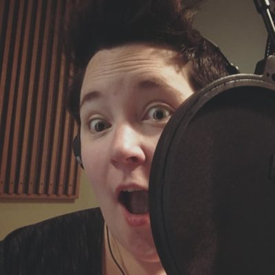 Kirsten in a recording studio wearing a grey top and black over ear headphones; she's making a surprised face next to a microphone with buffer