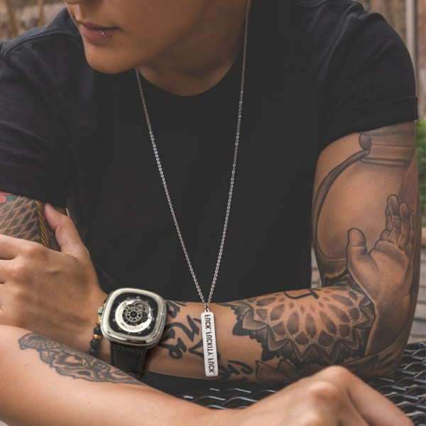 man with tattoos wearing big futuristic watch
