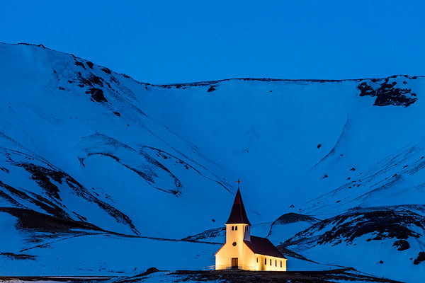 Vik i Myrda church lit up at dusk in Vik, Iceland