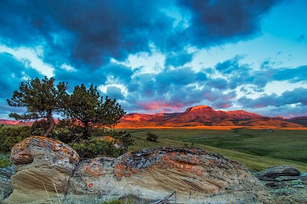 Fiery sunrise light strikes Ear Mountain along the Rocky Mountain Front near Choteau, Montana