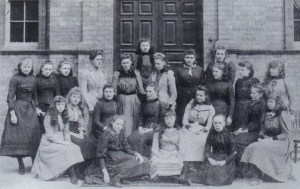 Newcastle High School girls around the time of the new building's opening, with the two dedication stones visible either side of the side-door (traditionally always the pupils' entrance) behind them.