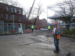 The red crane now hovers by a pile of newly delivered steel for the new extension.