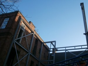 Close-up view of the extension steelwork against bright blue sky.