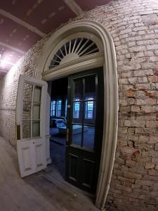 The semi-circular glass fan lights above doors.