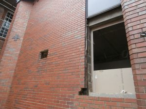The Science Wing brickwork may be full of holes, but the bronze commemoration plaque is still in place.