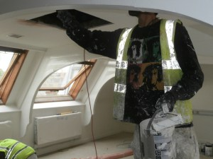 On May 18th, the painters were at work applying the ubiquitous white emulsion. The hatch in the ceiling Just behind the painter's right arm, is actually the original Victorian fresh-air ventilation shaft.