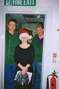 Gentian Qeku, then a young man fresh from Kosovo, and Dave Stout pose with Jane Grundy on a Staff Pantomime afternoon.