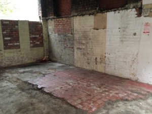 Remains of an old red-tiled floor in the north gable kitchen area.