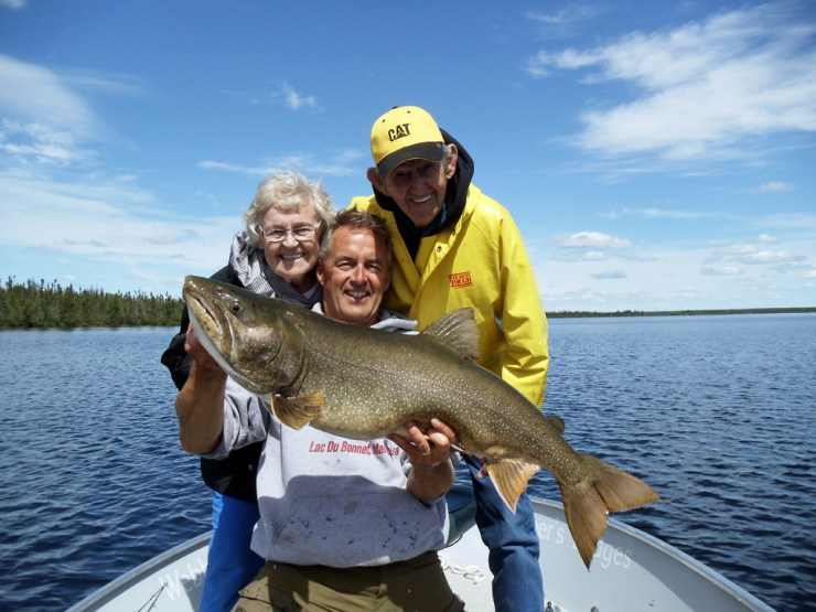 Mike Reimer with Mom Myrtle and Dad Melvin and trophy lake trout (nice catch Mom!) at North Knife Lake Lodge.