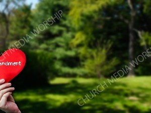 Child holding paper heart - Commandment Christian Worship Background. High quality worship images for use to spread the Gospel and enhance the worship experience.