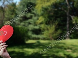 Child holding paper heart God Christian Worship Background. High quality worship images for use to spread the Gospel and enhance the worship experience.