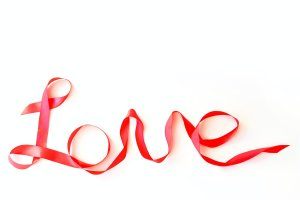 The word love written in red silk ribbon on a white background