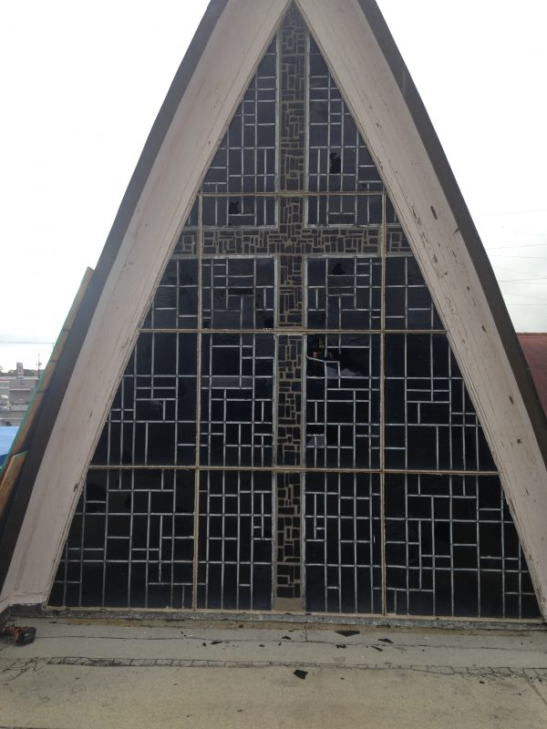 The massive cross stained glass has multiple large holes from hail damage