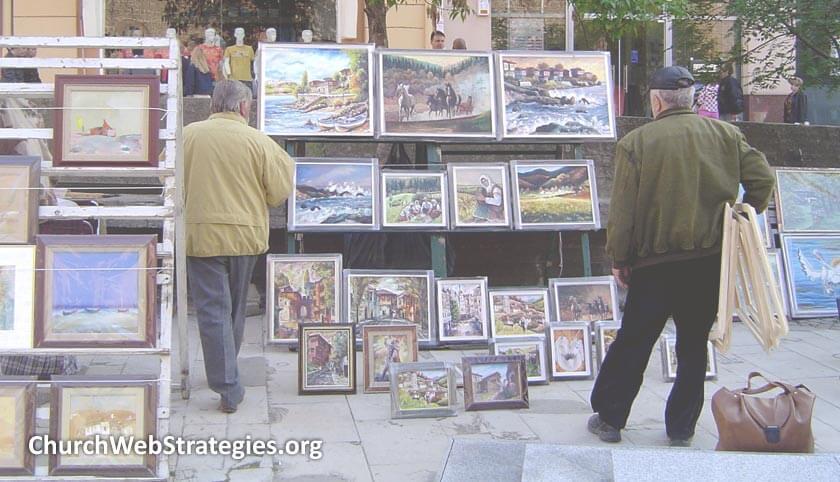 men browsing paintings at street-side sale