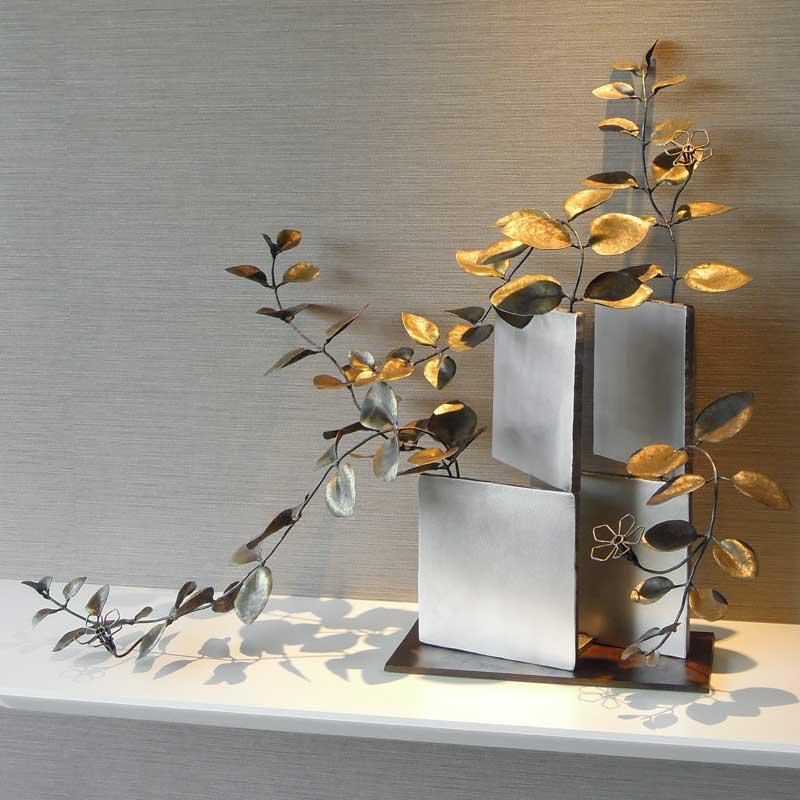 厚みのあるステンレス板の隙間からツルニチニチソウが伸びている様子を鍛鉄で表現したアート作品。花はワイヤーワークになっています。