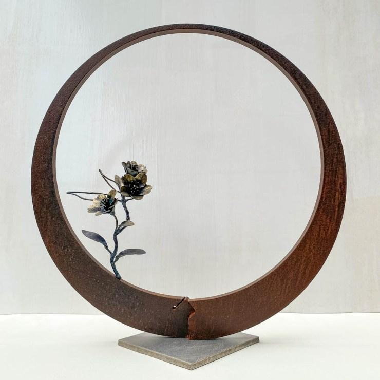 箱根に咲くマメザクラの小さな枝が、丸いベースに添えられた鉄の彫刻です。かわいい花が鉄で繊細に表現され、新芽が芽吹いています。