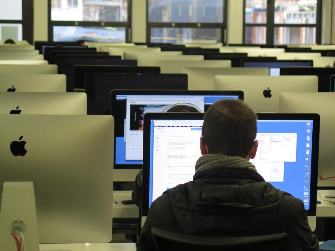 Student working in front of the computer within the classroom