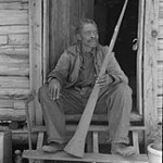 African American in Front of a Log Cabin