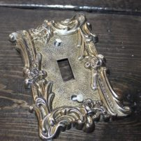 BEFORE: Dated gold switch plate