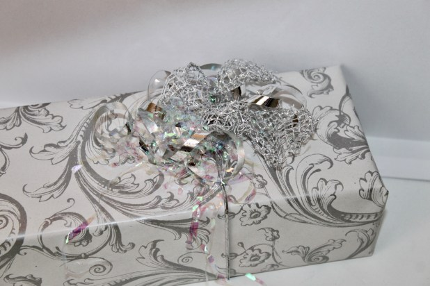 Re-used elastic ribbon, a dollar store netted wire bow, silver curly ribbon and a few strands of iridescent present stuffing are used to create this beautiful gift.