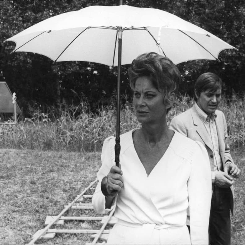 un ritratto di Alida Valli sul set con un ombrello bianco