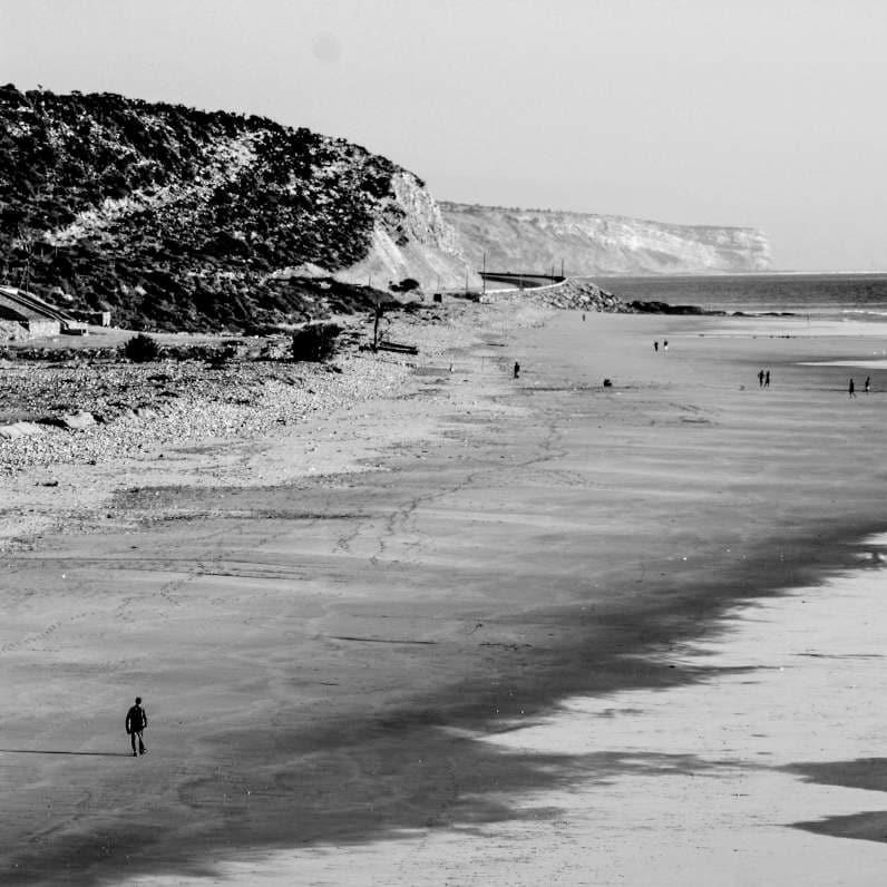 un uomo cammina in riva al mare vicino a delle scogliere a falesia