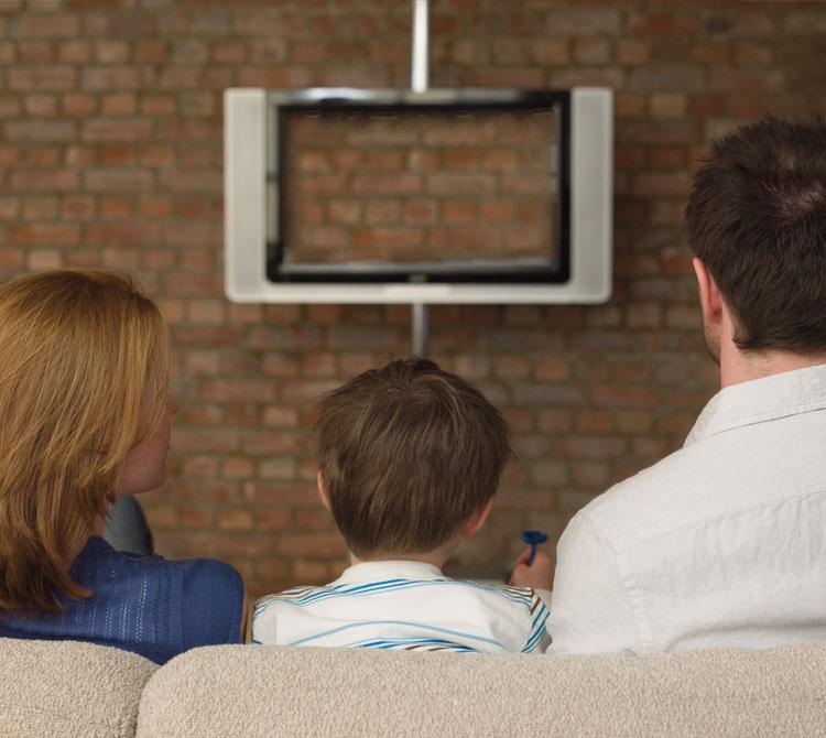 Umani della terra che fissano un televisore.