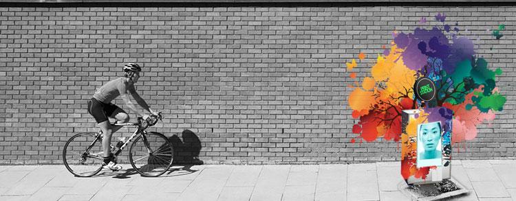 Uomo in bici davanti ad una stazione di stampa