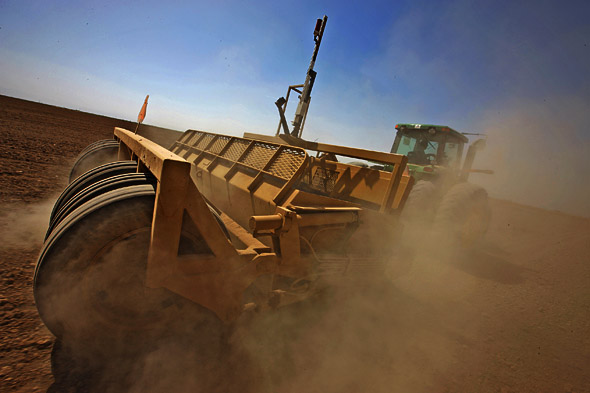 Farmers use tractors with laser surveying gear towed behind as they map out a new field on a farm in Imperial Valley, California.