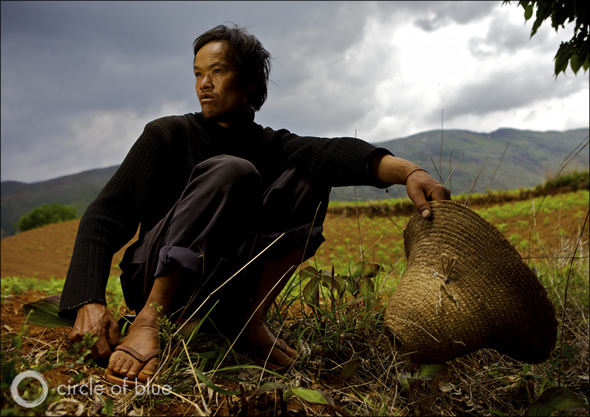 Photo © J. Carl Ganter / Circle of Blue A farmer outside Qibudi in China's Yunnan Province surveys his field. Although it has been raining for days, the same field, where karst stone is beginning to poke through the topsoil, turns dry for eight months of the year. He carries household water three times daily from a hillside pond. He and his elderly father make due on six buckets of water each day.