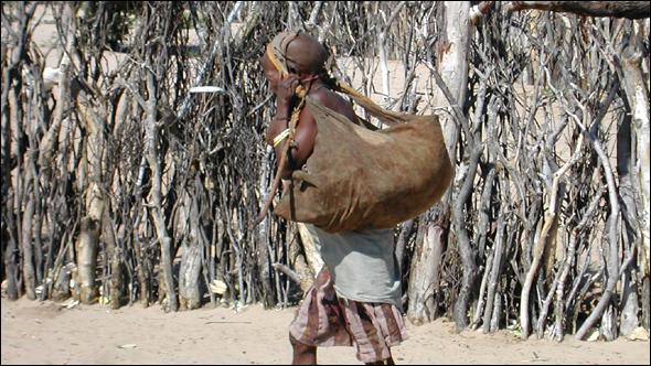 Kgaga bringing supplies to her hut.