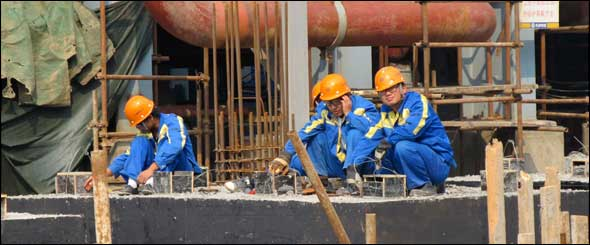 Chinese workers rest at the construction site of Tianjin's GreenGen coal-fired gasification power plant, scheduled to start operations in 2011. The project is at the head of a pack of Chinese power plants designed to burn coal more efficiently, use less water, and develop and prove carbon capture and storage techniques.