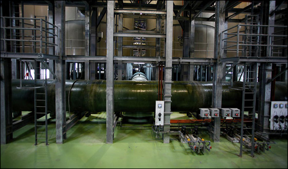 A mass of plumbing, pumps, scaffolding, and remote sensors move water from brown to blue at the Changi plant.