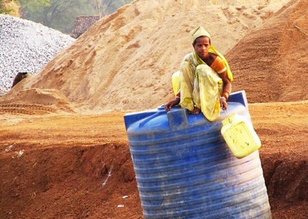 A water transport construction worker rests atop a bulk water container near Tilda, northwest of Raipur in Chhattisgarh, India.