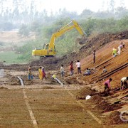 Workers swarm a big water transport canal near Tilda, India undergoing repair and expansion to serve the steam production and cooling requirements of the region's expanding number of big coal-fired power plants.
