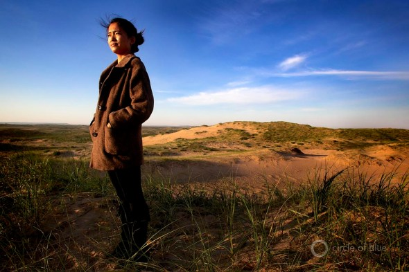 Wu Yun, 25, stands atop sand dunes that are advancing across her family's farm in the grasslands of Inner Mongolia.