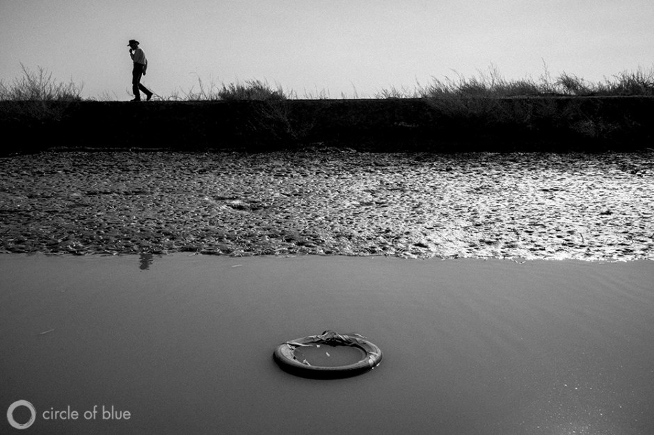 John Burchard, general manager of the Alpaugh Community Services District, walks a ditch bank on the outskirts of town. The small farmworker community in California's Central Valley suffers from high levels of arsenic and other contaminates in its drinking water.