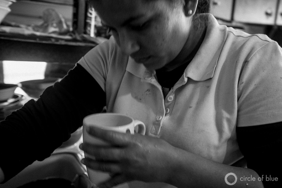 Evilia Robles inspects drinking water at her home in Alpaugh. The small farmworker community in California's Central Valley suffers from high levels of arsenic and other contaminates in its water.
