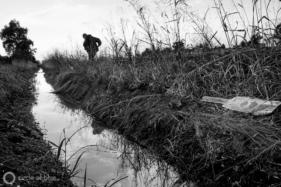 Becky Quintaña, a community water activist, walks along a canal near her home in Seville, a small town in California's Central Valley. One of her community's main domestic water supply lines runs along the bottom of this canal and frequently breaks. One of Quintaña's family members was brushing his teeth in the morning when a tadpole came though the faucet and into the bathroom sink.
