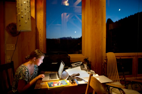 Lily Janssen uses her computer just after the sun has set behind the mountains in their front yard. Her father Robb says that he wants to try to conserve energy use, but he still wants it to be bright enough to …try and live a semi normal life.