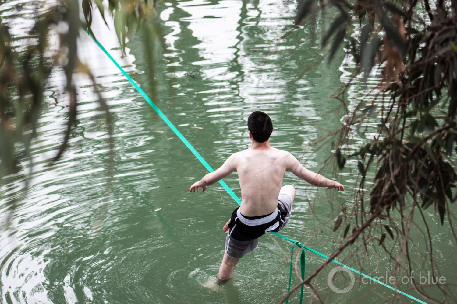 A teenager balances on a slack line looped between trees across the Jordan River, near Lake Kinneret. Though monumental in history and politics, the Jordan is not a large river. Photo © Brett Walton / Circle of Blue