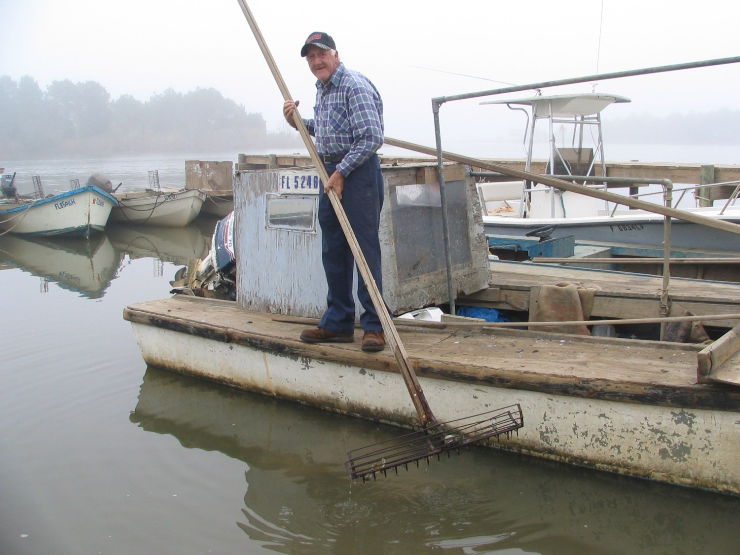 An oysterman rakes his harvest on the Apalachicola Bay. The health of the bay is at the center of Florida's lawsuit against Georgia. Photo courtesy Flickr/Creative Commons user Southern Foodways Alliance