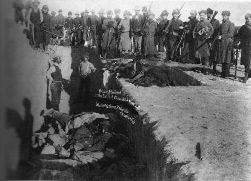 Burial after the massacre of Wounded Knee. U.S. Soldiers putting Native Americans in mass grave. Photograph from w