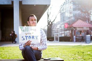 Jonny and his Tell Me Your Story sign representing Circle of Hope church in Philadelphia.