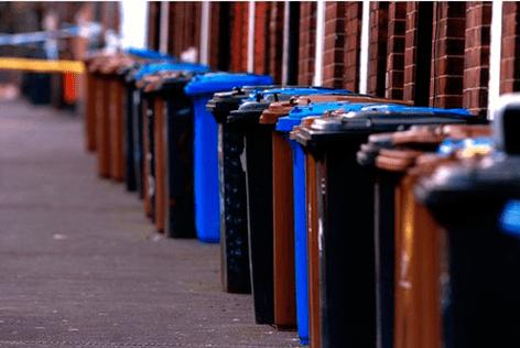 blue black brown bins in street