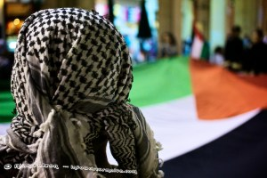 A Palestine wearing traditional head scarf in front of a large Palestinian flag