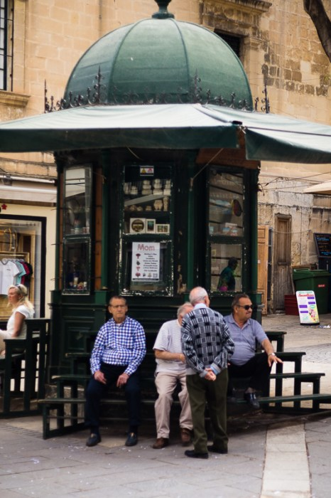 Old men chatting near a wooden shop. Valletta