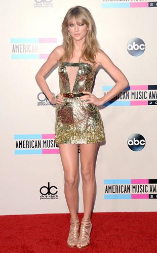 Para fechar, Taylor Swift, literalmente brilhando no seu gold dress